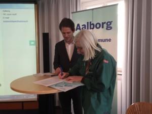 Birthe Schou underskriver på vegne af BUS Charter med rådmand Mads Duedahl fra Aalborg Kommune